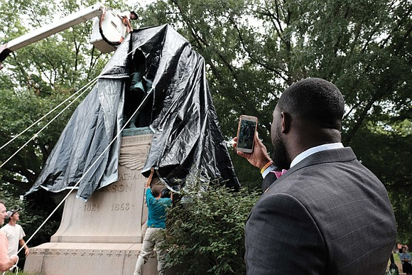 Workers in Charlottesville draped giant black tarps over two statues of Confederate generals on Wednesday to symbolize the city's mourning ...