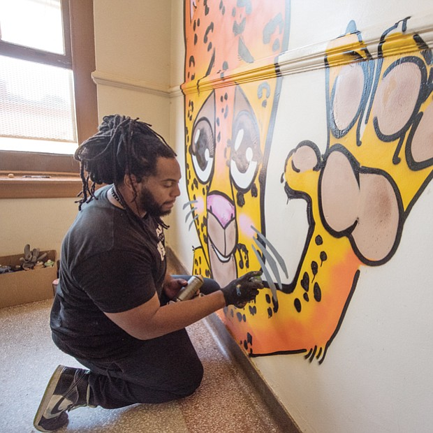 Silly, a local artist, paints the school's mascot, a Jaguar, on the landing of a stairwell.