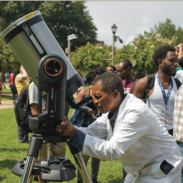 Solar phenomenon // use approved eclipse glasses to view the event from the T. Tyler Potterfield Memorial Bridge in Downtown. Dr. Francis E. Mensah, assistant professor of physics at Virginia Union University, sets up on the university's lawn as spectators gather to view the eclipse.