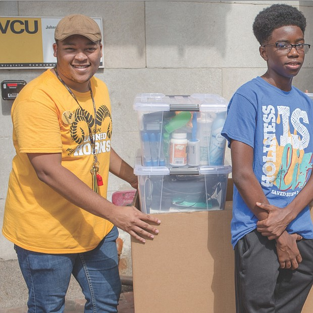 A new wave of freshmen has arrived on Richmond's college campuses, often accompanied by their families. William P. Agble of Fredericksburg, third from right, moves a cartful of belongings Saturday into Johnson Hall at Virginia Commonwealth University, with help from his family and a student volunteer, left.  Surrounding him, from left, are brother Josh, sister Jemima holding his guitar, father William K. Agble, mother Susie Agble and sister Kaitlyn. William and other students started classes at VCU this week.