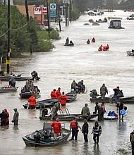 Rescue boats fill a flooded Houston street to reach Hurricane Harvey survivors.  (AP photo)