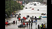 Rescue boats fill a flooded Houston street to reach Hurricane Harvey survivors.  (AP photo)