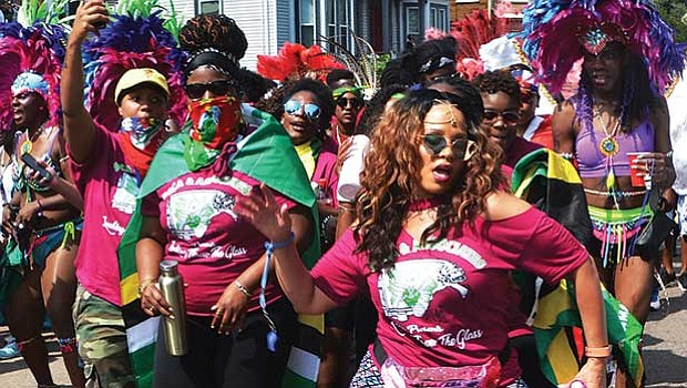 Members of the Soca & Associates masquerade band dance on Warren Street during Boston's Caribbean Carnival.