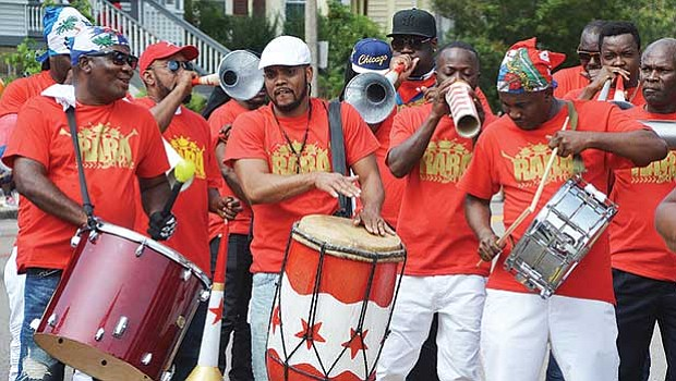 Members of a Haitian band use drums and improvised horns and percussion instruments.