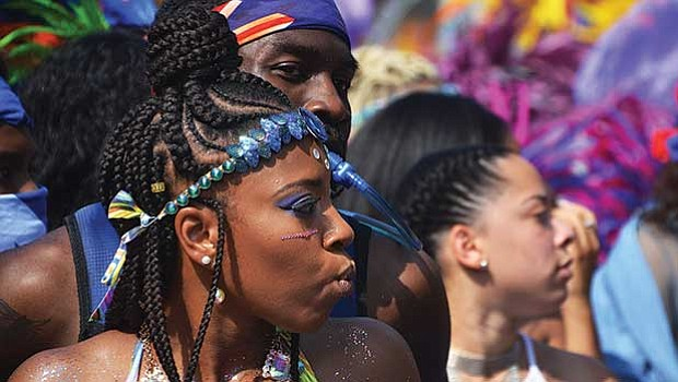 Spectators and masqueraders mingle during Carnival.