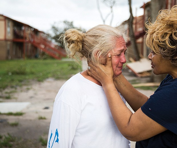 Genice Gipson, right, comforts her lifelong friend Loretta Capistran, outside Ms. Capistran's apartment complex in Refugio, Texas, on Monday.