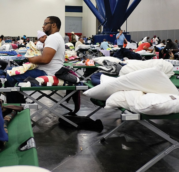 People displaced by the hurricane take shelter in the Houston Convention Center as the slow-moving storm inches its way through Southern Texas on Tuesday.