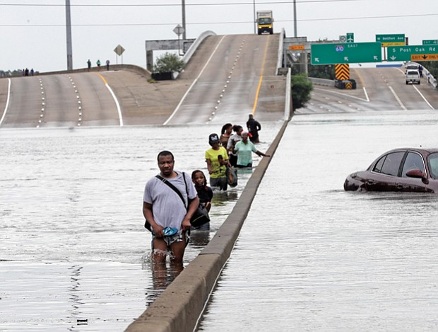 Evacuees wade down a flooded section of Interstate 610 as floodwaters rise Sunday in Houston.