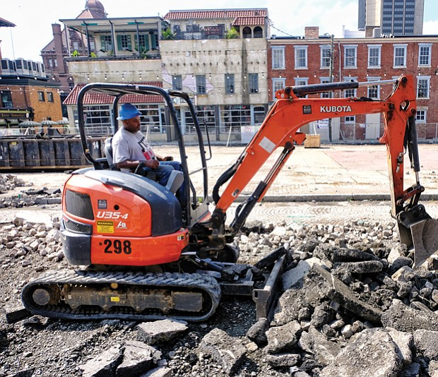 A worker digs up cobblestones that covered a now closed stretch of 17th Street in Shockoe Bottom. The work is part of the estimated $4.3 million facelift for the Farmers' Market area, which dates to the 1780s and is among the oldest such marketplaces in the country. The old pavilions, concrete and stones are being removed between Main and Franklin streets to create a European-style plaza with market stalls on the side and an open space for local and regional events. The outdoor setting that is to be finished next year is designed to complement the revamped Main Street Station with its grand indoor event space. Despite the work, businesses located along the street are still open and accessible by the sidewalk.