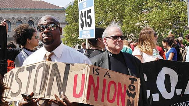 Boston Teachers Union Political Director Johnny McInnis (left) and others display signs and banners at a Labor Day rally for higher wages and union rights in Copley Square.