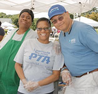 """Lawnside New Jersey, Parent Teacher Association member, Gloria """"Miss Sissy"""" Johnson and President, Debbie DeAbreu with Councilman for Lawnside Ron DeAbreu were serving free hot dogs and burgers to parents and students."""