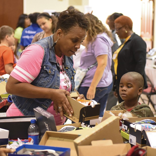 Sharon Toulson of Sharon Baptist Church helps 4-year-old Joshua Ellis choose the perfect pair of shoes.