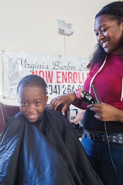 Old school party for new school year //  Antonio Daniels, 7, gets his hair cut by Zeymoria Light,
