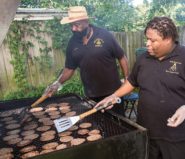 Alonzo Coley keep a watchful eye on hamburgers cooking on the grill at the event hosted by members of the 26th Masonic District and the Richmond Police Department in Church Hill.