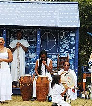 Patricia Chalinaru Dones (right), representing a Taino native, gives her blessing to the Cabin/Praise House created by artist/performer Ife Franklin (left) Sunday, Sept. 10 at Franklin Park.