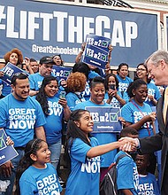 Gov. Charlie Baker shakes hands at a 2016 Great Schools Massachusetts rally in favor of lifting the cap on charter schools.