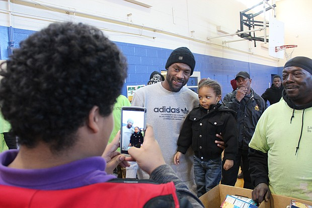 Tony Allen poses with a young fan as the Grizzlies donated turkey baskets to Frayser families for the 2016 holiday season.