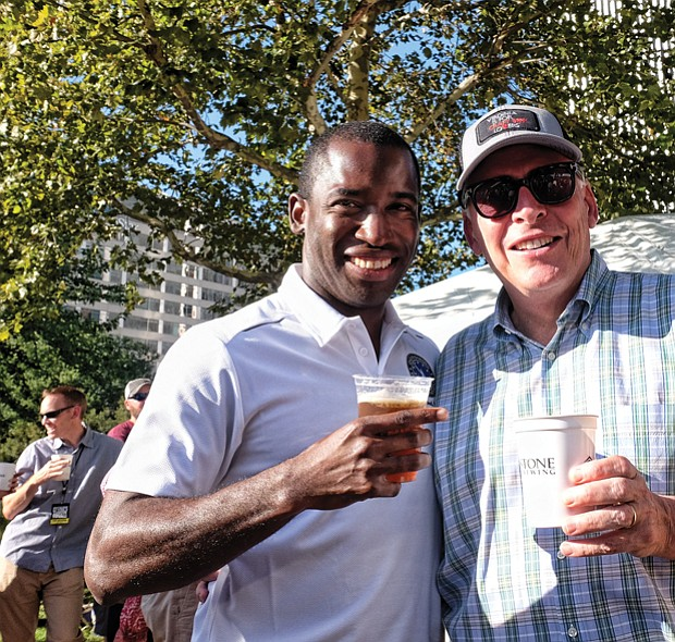 Richmond Mayor Levar M. Stoney, left, and Gov. Terry McAuliffe enjoys a drink in the sunshine during the daylong event featuring six bands.
