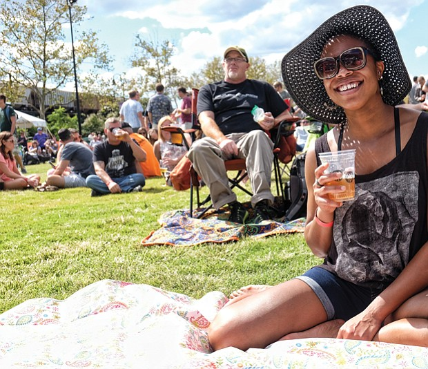 Stephanie Williams, right, enjoys a drink in the sunshine during the daylong event featuring six bands.