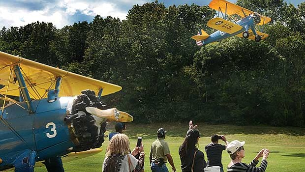 Guests watch as donors take flight on the refurbished WWII PT-17 Stearman