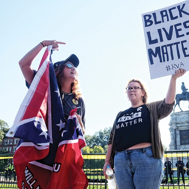 Tara Brandau, a Florida resident and organizer with the pro-Confederate CSA II group, expresses her support for the Lee statue while counterprotester Taylor Medley holds a sign with her opposing sentiment.