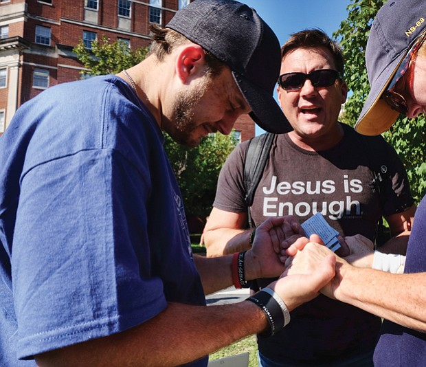 Jason Collier joins the hands of a protester and counterprotester to pray near the Lee statue in the midst of the rally.