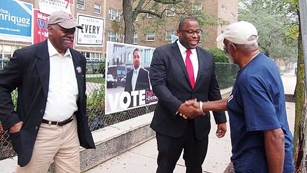Mayoral candidate Tito Jackson, accompanied by Louis Elisa (left) greets James Woods (right) before voting at the Holgate Apartments on Elm Hill Avenue in Roxbury.