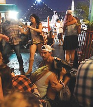Concertgoers run over barriers and duck for cover when gunfire from a sniper perched in a nearby hotel aims his firepower at a concert venue along the Las Vegas strip on Sunday, killing 59 people and injuring more than 500.