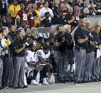 Oakland Raiders players kneeling in week three of 2017 NFL season. Wikipedia photo.