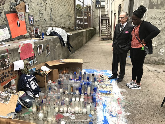 Candles and photos of 15-year-old Matthew McCree are still visible in the backyard of his apartment building on Mapes Avenue ...