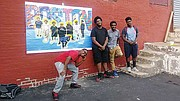 "Teens who are depicted in ""Saints"" pose with the work."