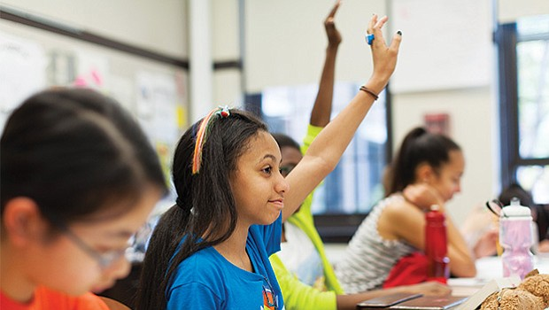 Students raise their hands in a Winsor School classroom.