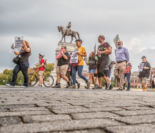Rallying for rights // Coalition for Accountability members gather last Tuesday near the Robert E. Lee statue on Monument Avenue and walk to Shockoe Bottom to demand the removal of Confederate statues, better schools, expanded public transportation and immigration and LGBTQ rights.