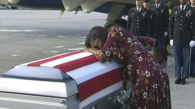 """In this Tuesday, Oct. 17, 2017, frame from video, Myeshia Johnson cries over the casket of her husband, Sgt. La David Johnson, who was killed in an ambush in Niger, upon his body's arrival in Miami. President Donald Trump told the widow that her husband """"knew what he signed up for,"""" according to Rep. Frederica Wilson, who said she heard part of the conversation on speakerphone."""