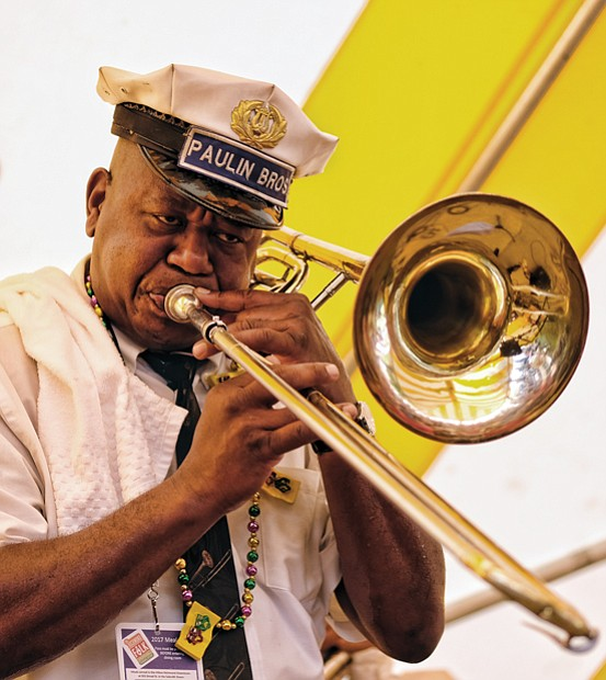 Folk Festival turns up lively music, crowd //  Dwayne Paulin, a trombonist for the Paulin Bass Band, plays traditional New Orleans jazz.