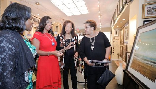LaBelle Art Gallery's Owner, Mame Young discusses the silent auction artwork on display to the fundraiser host and PHL 17 Tribune Broadcasting morning news anchor Jennifer Lewis-Hall and attendees Willa Chisler and Pamela James.