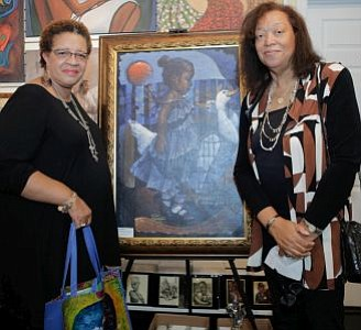 "Willa Chisler and Pamela James pictured next to one of the silent auction paintings, ""Girl In Blue"" Limited Edition on GICLEE by Lyonel Laurenceau."