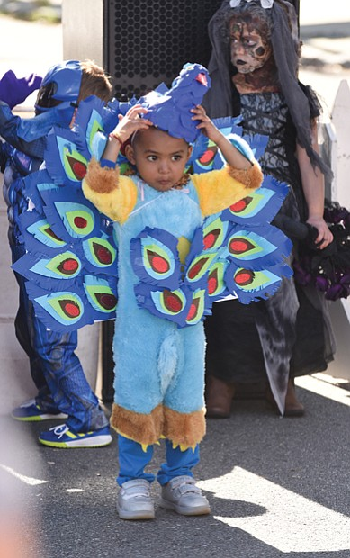 Getting in character // Aaray Kota, 3, adjusts the mask of his peacock costume, left, as he and other characters prepare for the Kids Costume Contest at the Scott's Addition Pumpkin Festival last Saturday on the Boulevard.