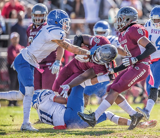 Wild with pride // Fans weren't let down. The VUU Panthers defeated the Elizabeth City State University Vikings 37-21. Below center, on this play, VUU freshman running back Tabyus Taylor hangs on to the ball as he's crumpled by the Vikings defense.