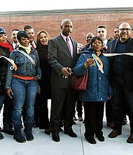 Elected officials and community members cut the ribbon to re-open The Yard at the Tobin Community Center. The $950,000 renovation provides community members an out-door meeting space, which has been dedicated to the late Ida Graves.