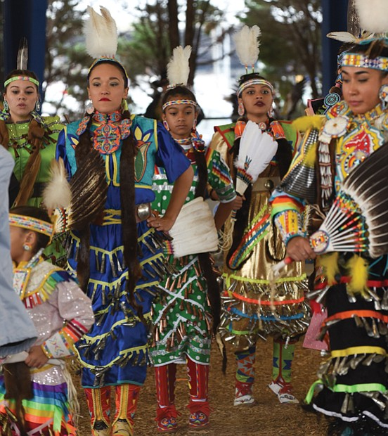 "Honoring ancestors and culture // Dancers in traditional dress perform the ""Honor Dance,"" memorializing members of their Native American tribes during the Great American Indian Expo last Saturday at Richmond Raceway."