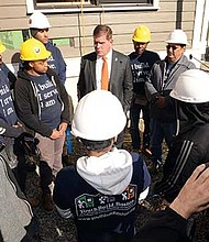Mayor Martin Walsh joins members of YouthBuild Boston, the Dudley Street Neighborhood Initiative and Madison Park High School students, and lends a hand in installing siding onto one of the City of Boston's Neighborhood Home Initiative homes being built at 31-33 Woodville Street in Dudley Square.