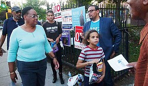 Campaign volunteers and candidates reach out to passersby at the Higginson-Lewis School polling location in Roxbury.