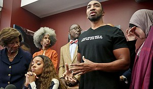 NAACP New York State Conference president Hazel Dukes, far left, comforts her god-daughter civil rights activist Tamika Mallory, seated second from left, while rapper and activist Mysonne Linen, second from right, speaks during a press conference at the office of Mallory's attorney Royce Russell, third from right, center, Oct. 17, in New York. Mallory, who helped organize the Women's March on Washington with civil rights activist Linda Sarsour, far right, has accused an American Airlines pilot of racial discrimination in kicking both her and Linen off a flight.