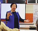 Suzanne Lee, co-chair of CCLT, translates for a community meeting at Josiah Quincy School.