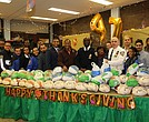 New York City Council Member Andy King (center in Brown), State Senator Jamaal Bailey (left of King), NYPD's Inspector Ruel Stephenson (right of King) and officers and volunteers prepare to giveaway frozen turkeys to families at the 47th Precinct.