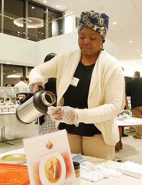 Participants in the Food Biz 101 pitch competition offered samples of their products. Paulette Ngachoko prepares portions of her Cameroonian peanut sauce.