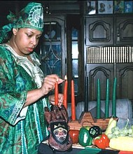 The Willingboro Kwanzaa Festival will be held from 11 a.m. to 2 p.m. at John F. Kennedy Center, 429 John F Kennedy Way, Willingboro, NJ. In photo, a woman lights kinara candles. -- Wikipedia photo