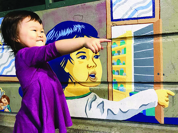 Mazzy Chiu stands in front of an image of her likeness that was created to celebrate cultural diversity for a Max Station mural on 82nd Avenue by her artist father Alex Chiu.