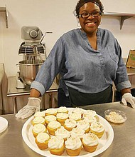 Teresa Maynard of Sweet Teez Bakery prepares a tray of vanilla cupcakes with cream cheese frosting and coconut cream frosting with toasted coconut flakes.